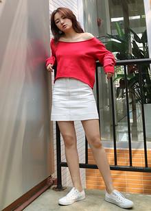 红色的宽松卫衣,衣领是卷边的,大大的可以一字露肩也可以斜肩穿,搭配白色短裙,很有女人味~